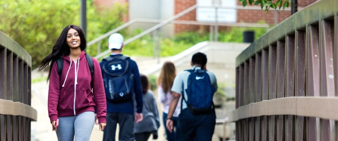 Student walking on scenic Pitt-Greensburg campus