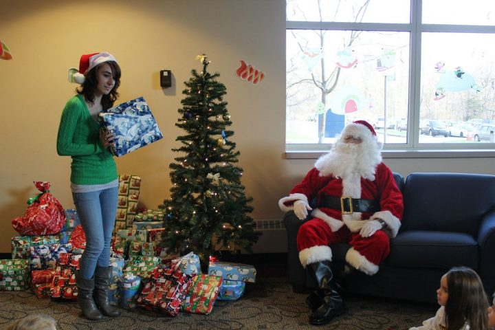 Volunteers hand out gifts to Head Start children at the annual Housing & Residence Life Christmas Party for local Head Start children.