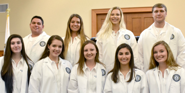 Nursing students in their white lab coats