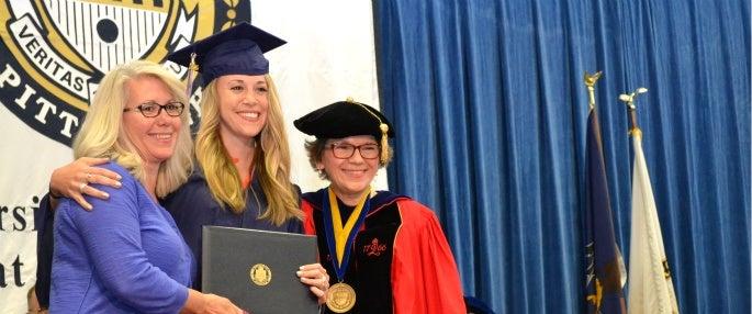 Pitt-Greensburg graduate posing with family member and President Sharon Smith