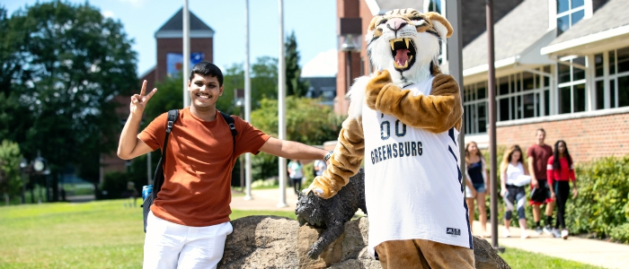Student posing with Bobcat mascot