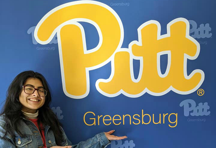 Student posing with Pitt-Greensburg sign