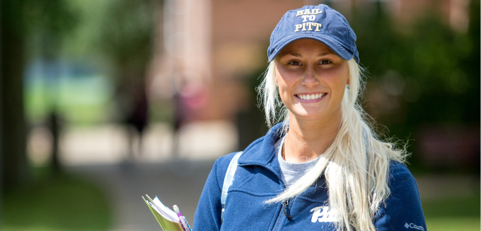 Female student in Pitt hat smiling