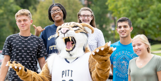 Five students posing with Bobcat mascot