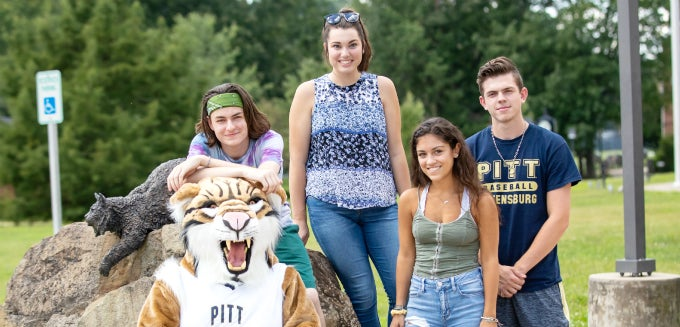 Four students posing with Bobcat mascot