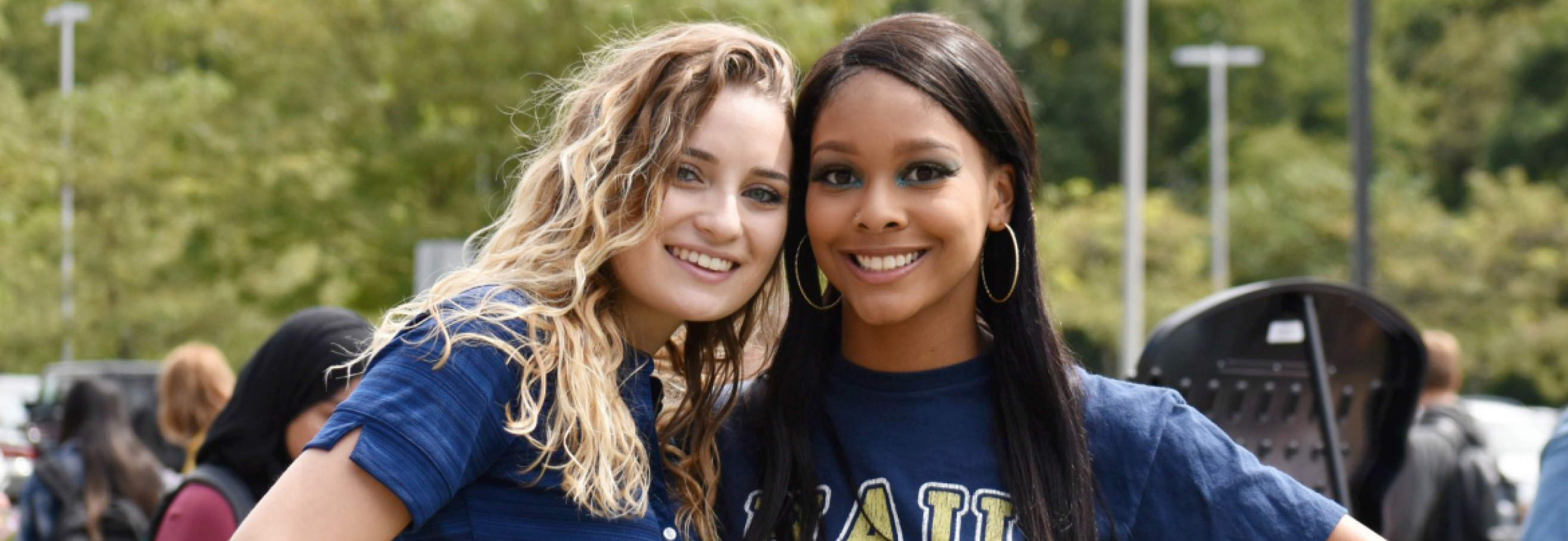 Two students in Pitt gear smiling for camera