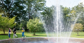 Three students walking by campus fountain