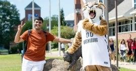 Student and Bruiser Bobcat mascot posing